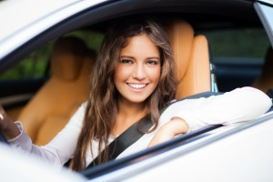 shutterstock_248941921-large-pic-Young-woman-driving-her-car-with-a-big-smile-and-arm-resting-on-the-window-seatbelt-fastened.